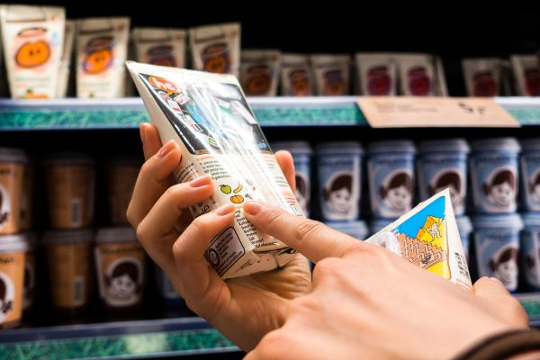 Person checking the food label in a supermarket and making an informed decision regarding how healthy a product is